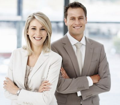 Two business executives smiling with hands folded